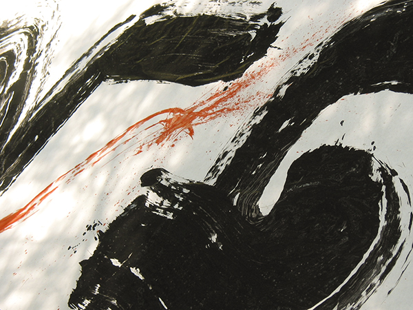 Closeup photograph of red and black calligraphy strokes on white paper using a big brush