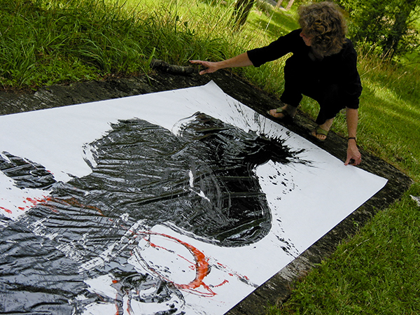 Long Medium shot photograph of black calligraphy stroke with red small stroke painted by Barbara Bash using a big brush on white paper outside on the grass