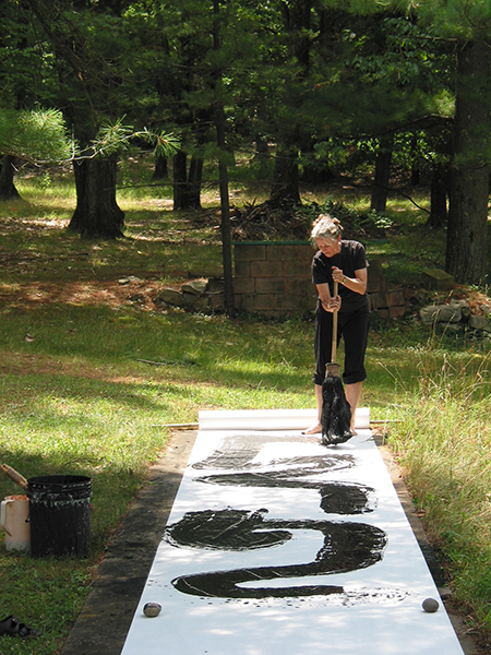 Long shot photograph of black calligraphy stroke painted by workshop participant using a big brush on white paper outside on the grass