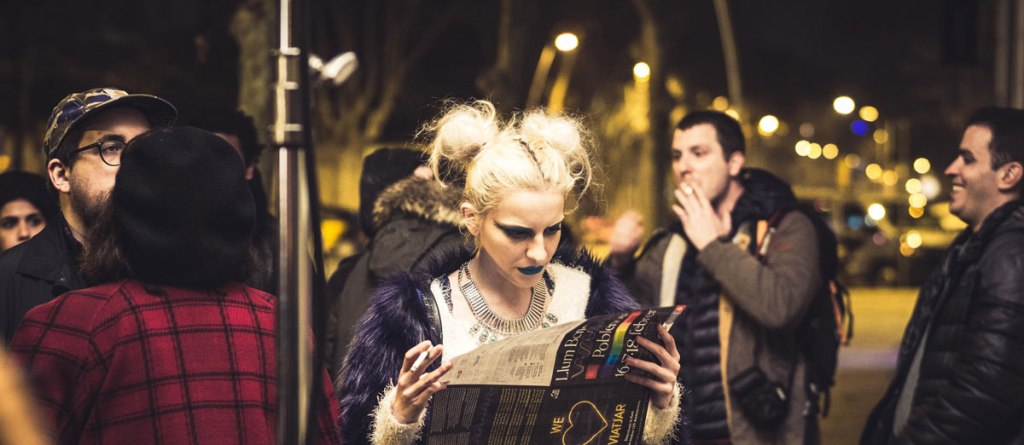 Photo of a young woman with blond ponytails, black lipstick, and a cigarette reading a colorful flyer in the midst of other people maybe waiting for a train